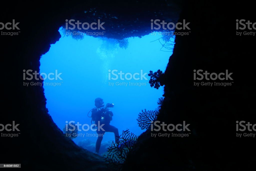 Diver photographing in the cave under the ocean floor stock photo