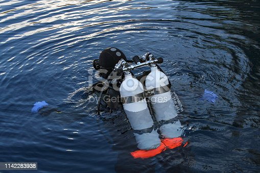 A scuba diver plunges into the dark water of a deep lake