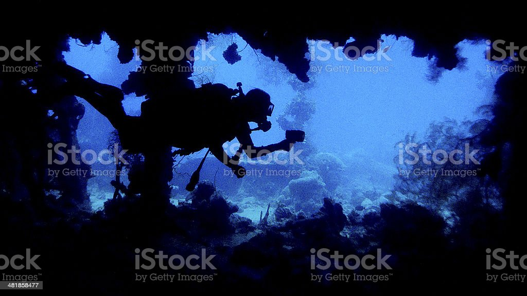 Diver sillohetted by wreck opening. stock photo