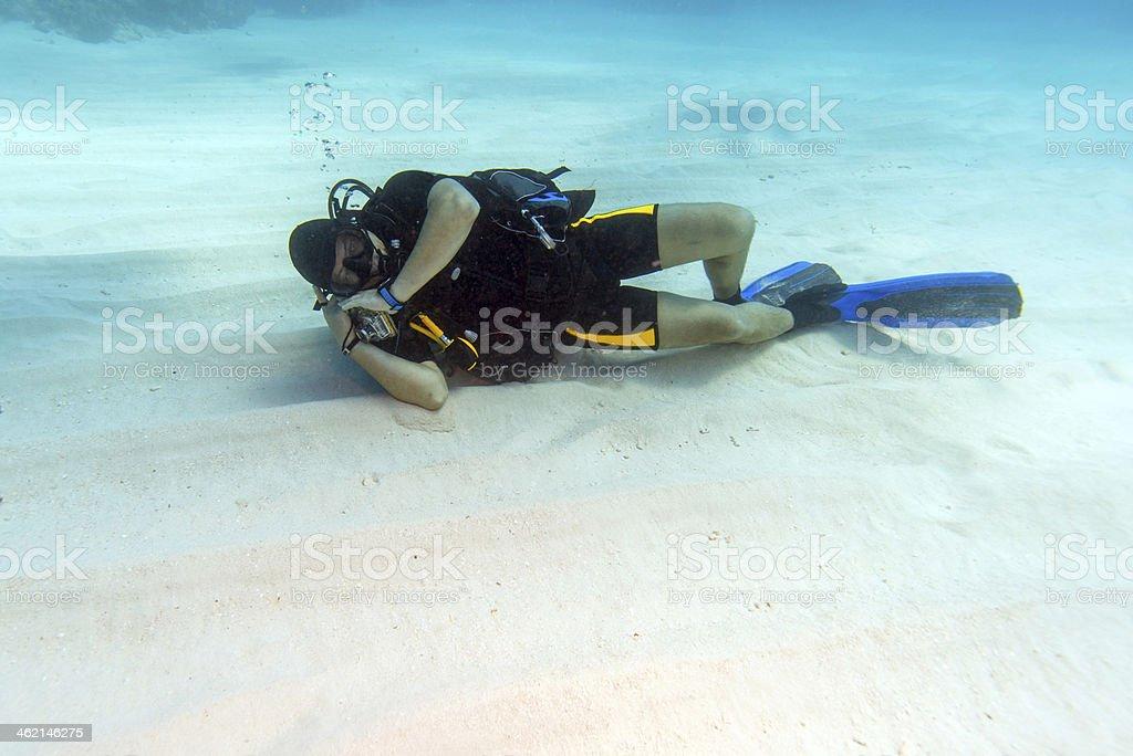 Diver Sleeping on Sandy Sea Bottom stock photo