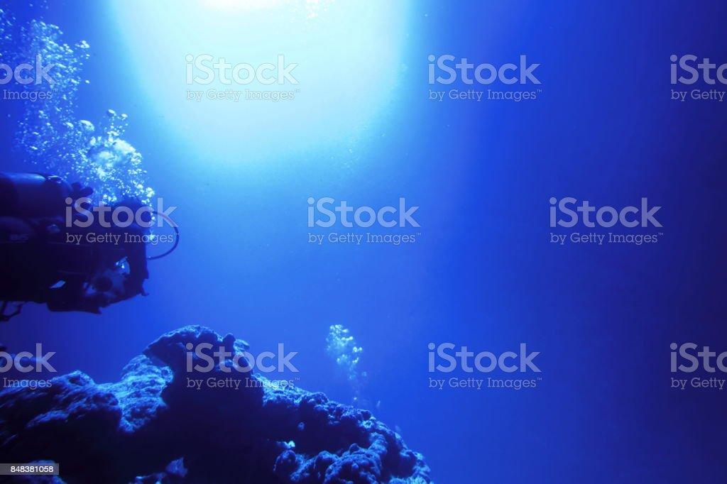 Diver swimming underwater and sunlight stock photo