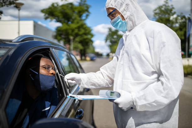 Diver through covid-19 testing Doctor in a protective suit taking a nasal swab from a person to test for possible corona virus infection on the street. Diver through covid-19 testing center in city. medical test stock pictures, royalty-free photos & images