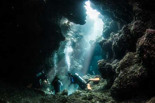 Scuba divers in a clear under water cave by the Kerama islands of Okinawa.