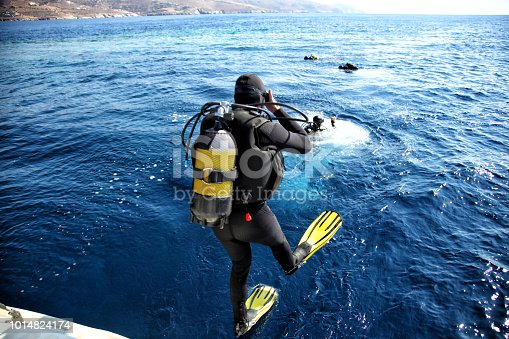 istock Divers jumping from the boat in water 1014824174
