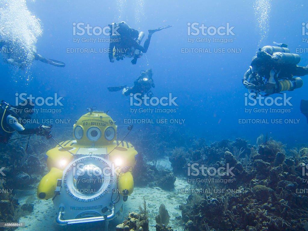 Divers surround submarine stock photo