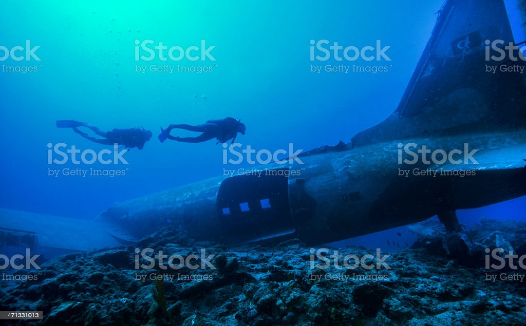 Divers swimming over the plane wreck stock photo