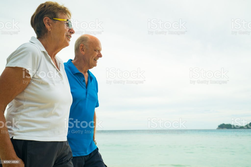 overcast day on the beach senior couple in their seventies walking...
