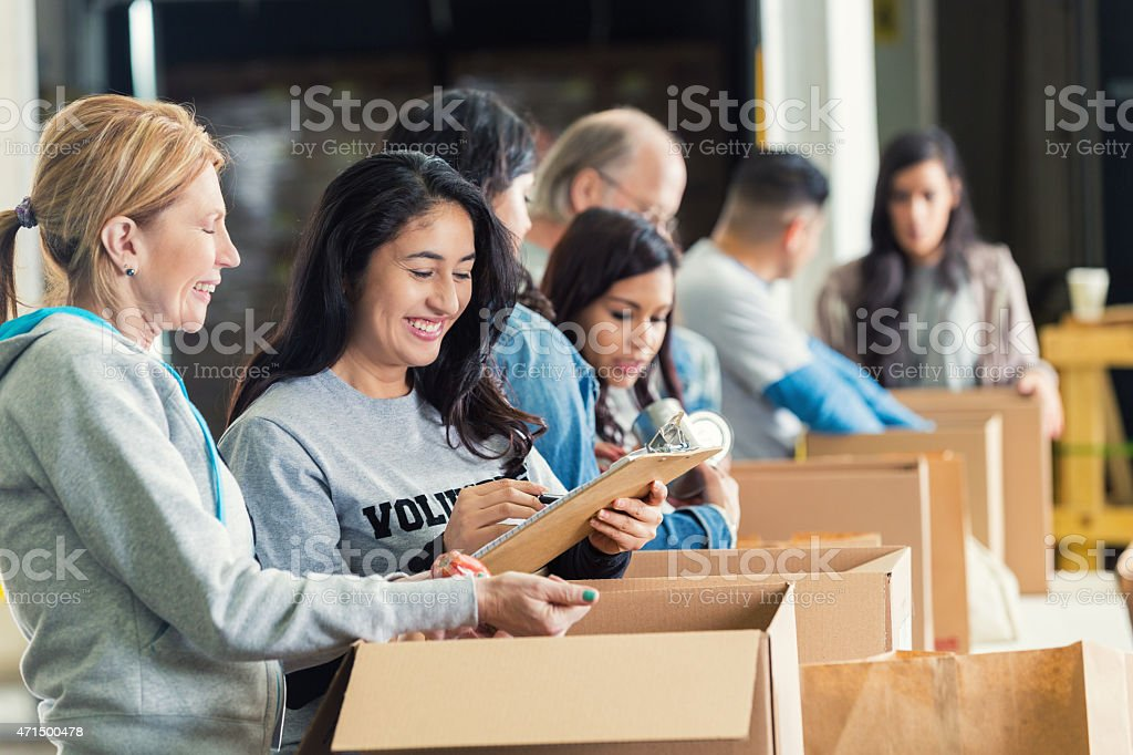 Diverse adults packing donation boxes in charity food bank stock photo