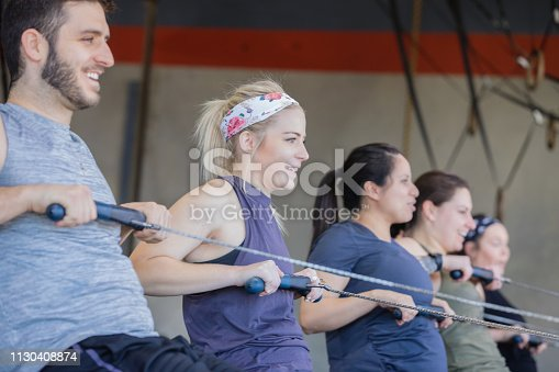 Diverse group of athletic en and women are using a rowing machine while working out in gym gym together.