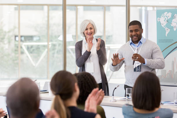 Diverse audience applauds African American keynote speaker After the introduction by the Caucasian moderator, the mid adult African American keynote speaker acknowledges the applause from the audience. college fair stock pictures, royalty-free photos & images