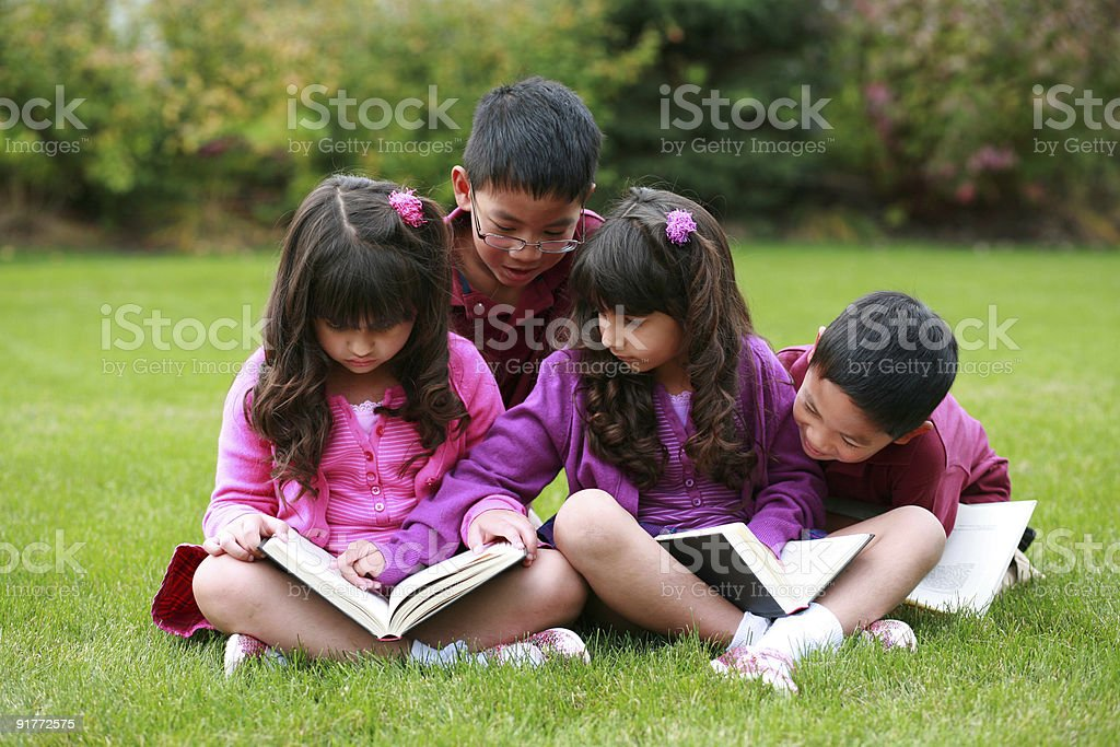 diverse boys and girls reading stock photo