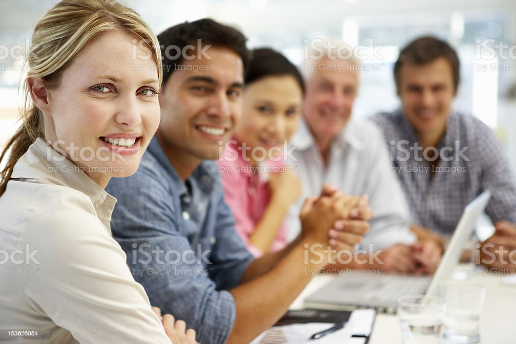 Mixed group in business meeting smiling to camera