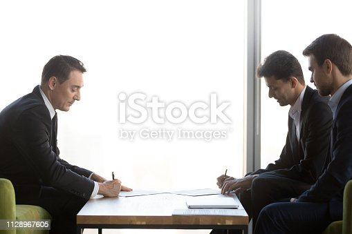 Diverse business partners signing two contracts making partnership agreement buying selling services at meeting, arabic and caucasian businessmen fill documents form put signature on legal papers