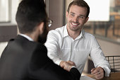 Multi-ethnic business partners before starting or accomplish negotiations shaking hands express respect, boss and applicant finish successful job interview hr first impression partnership sign concept