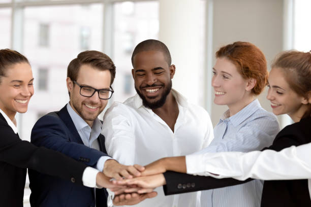 diverse business people group put hands together in stack pile - employee engagement stock photos and pictures