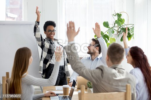 istock Diverse business people group raise hands at corporate presentation training 1127950022