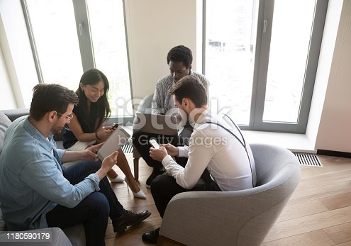istock Diverse business people using devices at meeting in office 1180590179