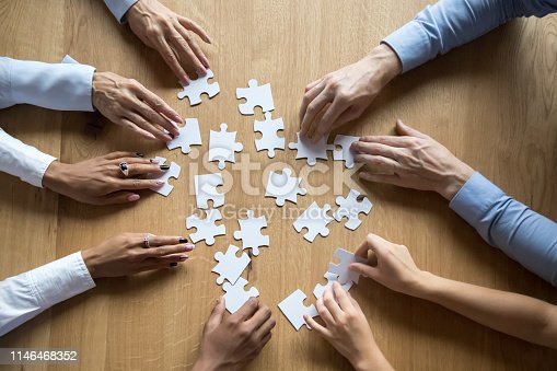 istock Diverse business team assemble puzzle together connect pieces at desk 1146468352