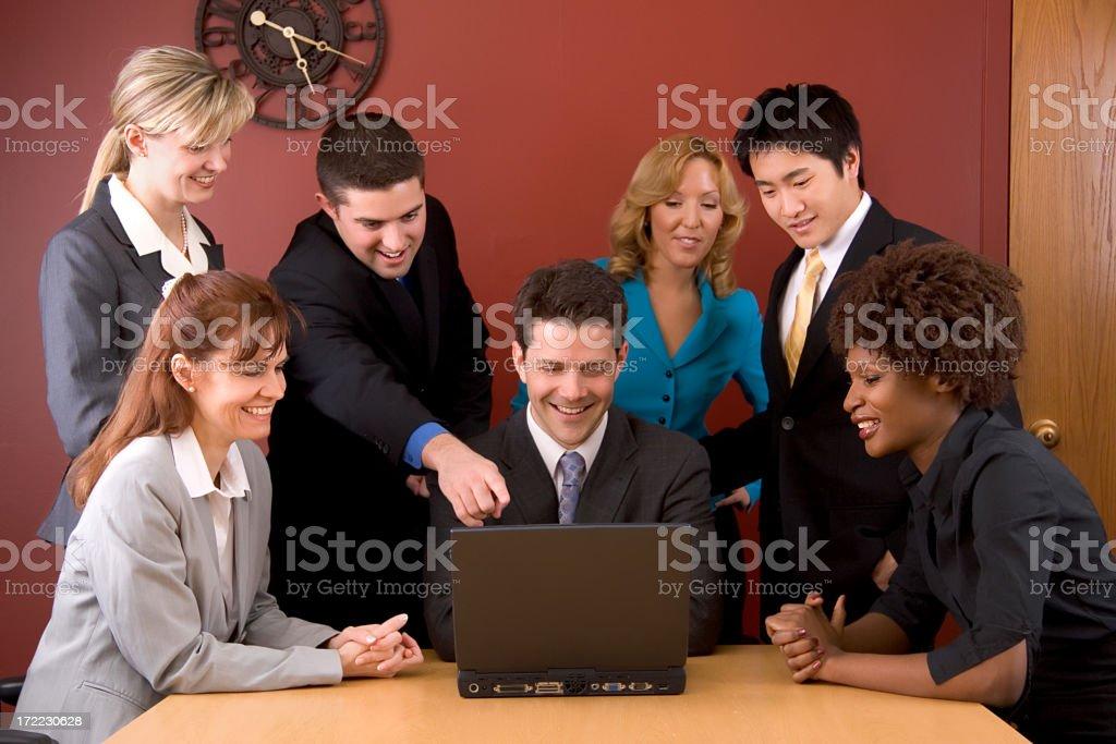 Diverse Business Team gathers around laptop royalty-free stock photo