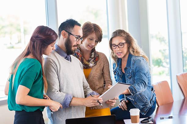 diverse business-team im büro während die legere strategien zu entwickeln - geführtes lesen stock-fotos und bilder