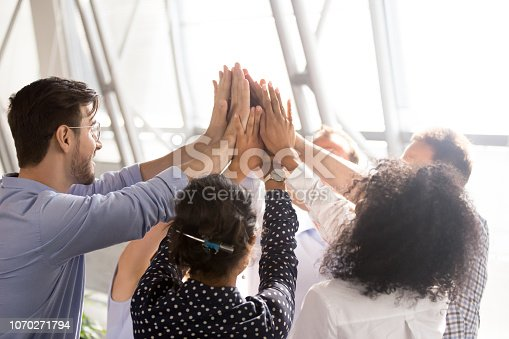 istock Diverse business team office workers group giving high five together 1070271794