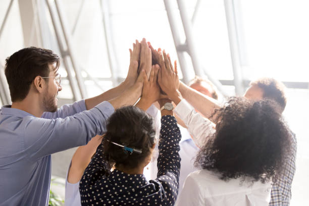 diverse business team office workers group giving high five together - employee engagement stock photos and pictures
