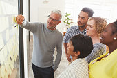Mature businessman and his diverse team brainstorming with yellow adhesive notes on a glass wall in a bright modern office