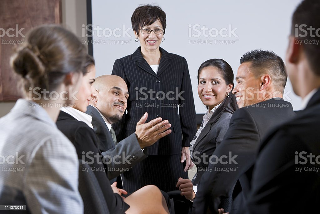 Diverse businesspeople conversing, woman at front royalty-free stock photo