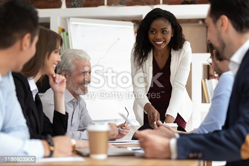 Different ethnicity and age businesspeople gathered together at boardroom for negotiations and planning future collaboration lead by african smiling businesswoman or corporate training process concept