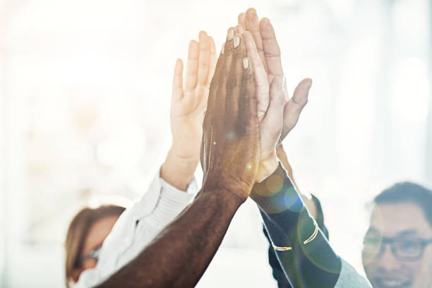 Diverse businesspeople high fiving together in an office - foto stock