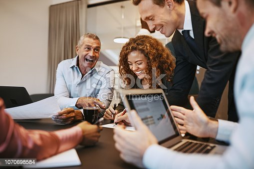 istock Diverse businesspeople laughing during a meeting together in an office 1070698584