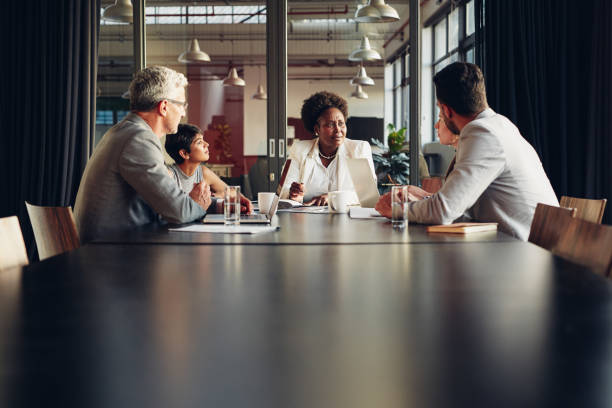 Diverse businesspeople sitting around a boardroom table discussing work stock photo