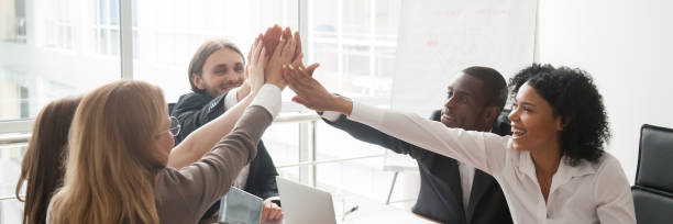 diverse businesspeople sitting at desk celebrating success giving high five - banner web foto e immagini stock