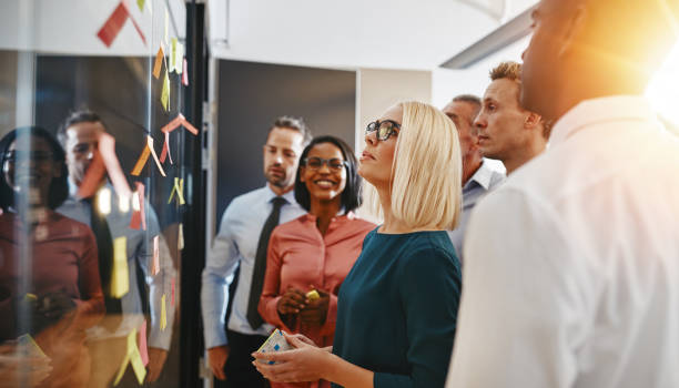 Diverse businesspeople standing in an office brainstorming with sticky notes Young businesswoman and her team brainstorming with sticky notes on a glass wall while working together in a modern office cooperation stock pictures, royalty-free photos & images
