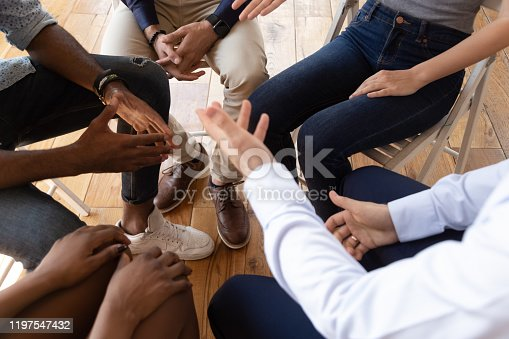 987123762 istock photo Diverse businesspeople talking seated on circle indoors closeup top view 1197547432
