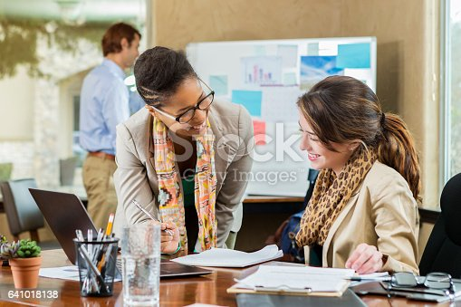 Cheerful mid adult African American and young Caucasian businesswomen discuss something in the office. They are reviewing documents at the Caucasian woman's desk. A man is working in the background.