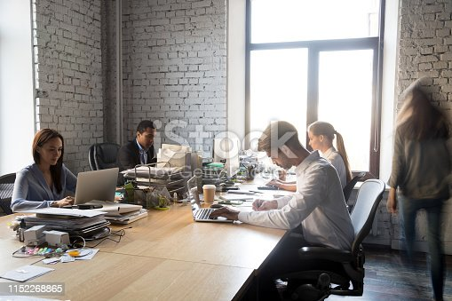 1090214584 istock photo Diverse busy coworkers working sitting at shared desk 1152268865