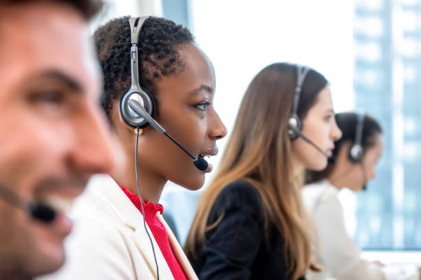 Diverse call center team working in office African American woman telemarketing customer service staff working with diverse team in call center office call centre photos stock pictures, royalty-free photos & images