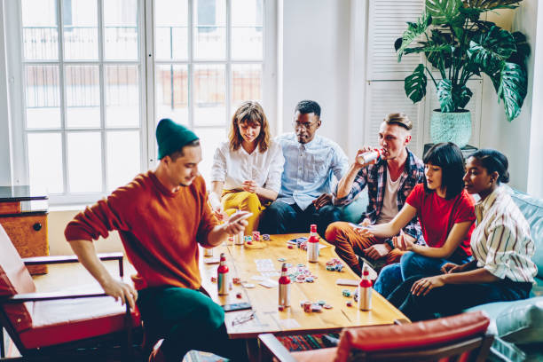 Diverse cheerful hipster guys drinking beverage and playing cards at table with chips for poker in modern apartment.Positive casual dressed multicultural friends spending free time together in flat stock photo