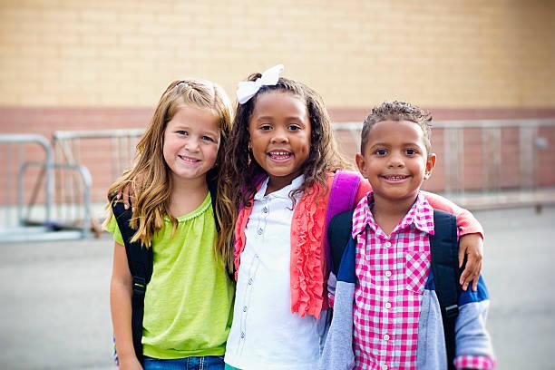 diverse children going to elementary school - yalnızca çocuklar stok fotoğraflar ve resimler