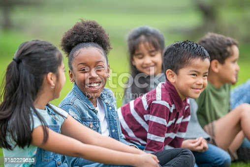 A diverse group of kids is sitting in a park and talking while they laugh about something that happened. They are all smiling while dressed in casual clothing.