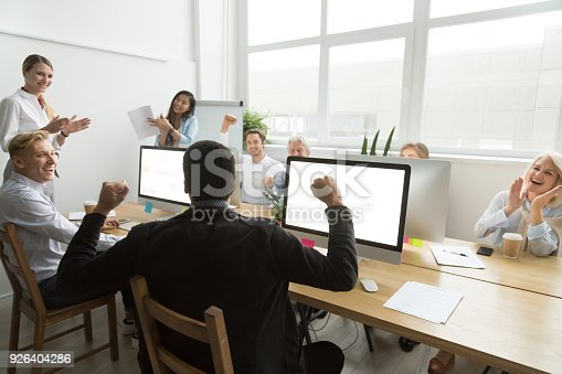 istock Diverse colleagues congratulating black coworker with good result or win 926404286