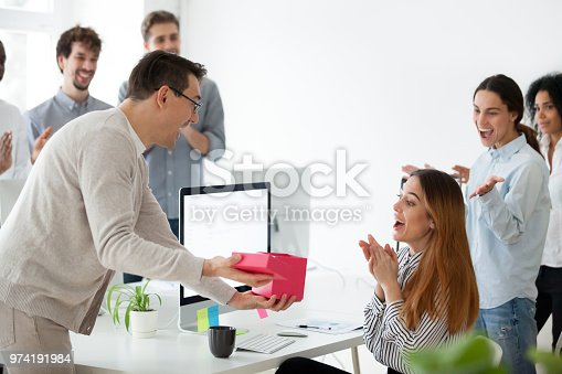istock Diverse colleagues congratulating surprised female worker with gift box 974191984