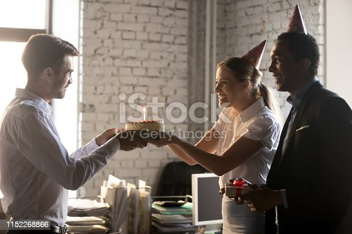 istock Diverse colleagues congratulating workmate with birthday giving cake with candle 1152268866