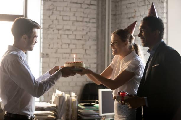 vielfältige kollegen gratulieren arbeitskollegen mit geburtstagskindern kuchen mit kerze - geburtstagsgeschenke für beste freundin stock-fotos und bilder