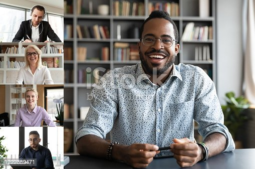 Smiling african American man worker talk brainstorm on video call with diverse colleagues, screen view of multiracial coworkers have webcam team work conference, engaged in web online briefing