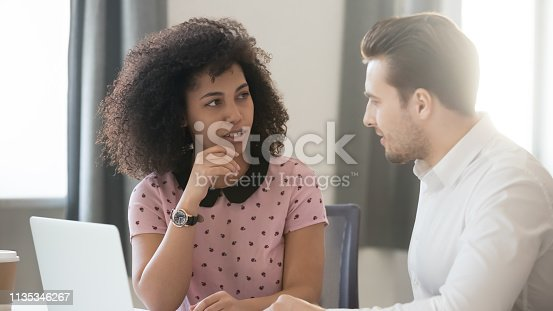 1085713886 istock photo Diverse colleagues talk in office working with laptop share ideas 1135346267