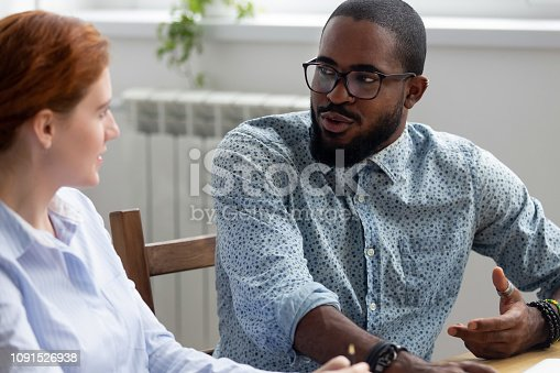 istock Diverse colleagues talking sitting together at office desk 1091526938