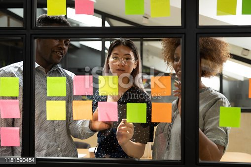 istock Diverse colleagues writing on sticky notes new project plan 1181590454