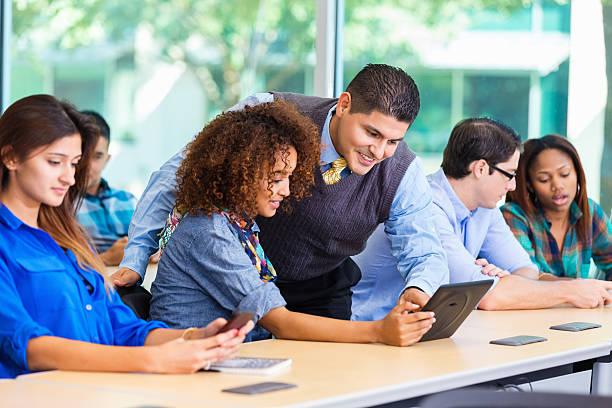 Diverse college freshman in class with Hispanic professor stock photo